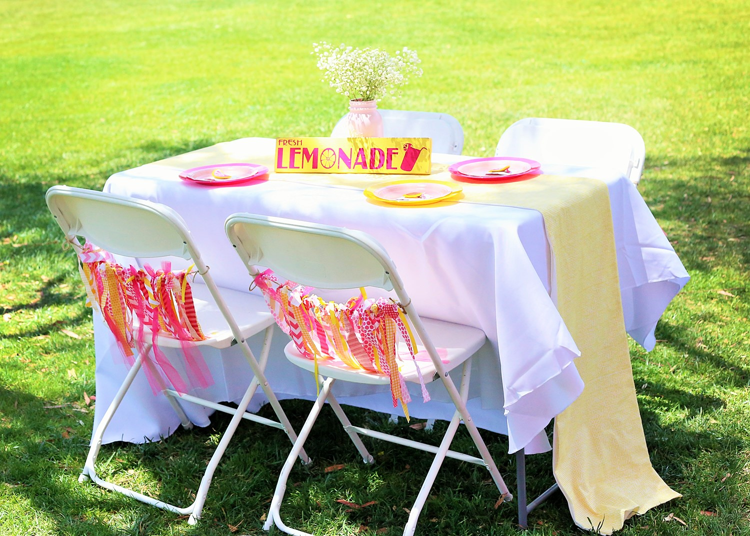 sunshine and lemonade party table with place settings and chair ties